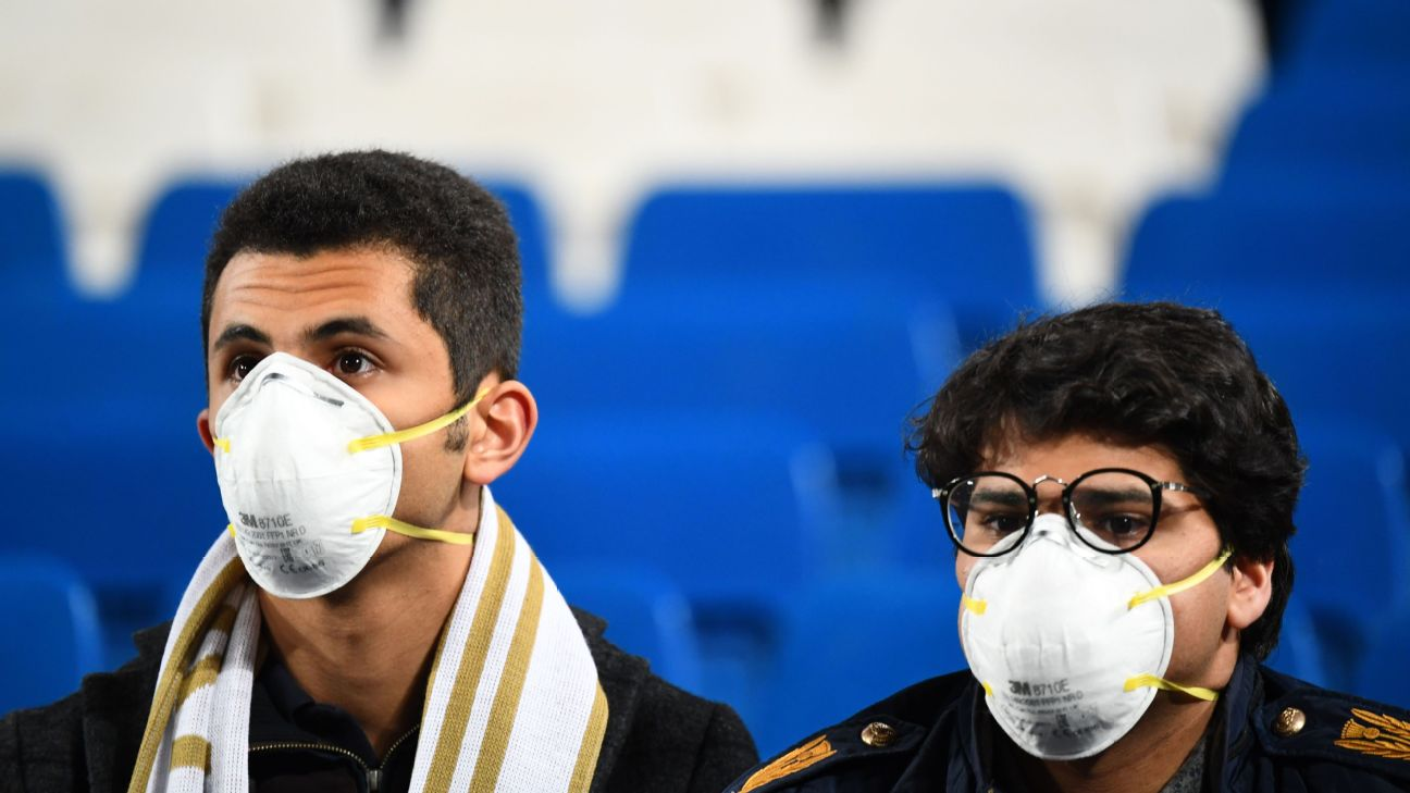 Football fans wearing masks in light of the coronavirus outbreak wait for the start of the Spanish League football match between Real Madrid and Barcelona