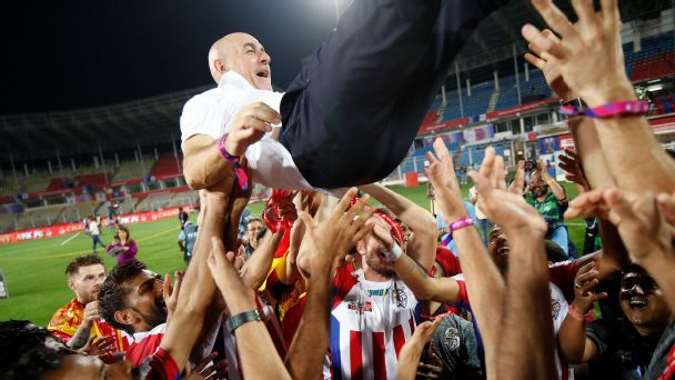 ATK players celebrate with coach Antonio Habas after winning the ISL final.